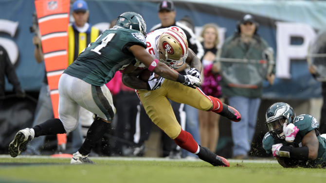 San Francisco 49ers tight end Vernon Davis (85) is hit by Philadelphia Eagles strong safety Jarrad Page (41) as outside linebacker Jamar Chaney (51) can't hang on, allowing Davis to score a touchdown in the second half of an NFL football game Sunday, Oct. 2, 2011 in Philadelphia. (AP Photo/Michael Perez)