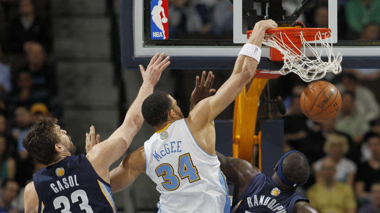 Denver Nuggets forward JaVale McGee (34) dunks for a basket past Memphis Grizzlies center Marc Gasol (33), of Spain, and forwards Zach Randolph (50) and Quincy Pondexter in the first quarter of an NBA basketball game in Denver, Friday, March 15, 2013. (AP Photo/David Zalubowski)