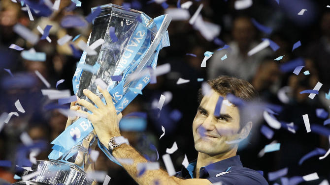 Roger Federer of Switzerland holds up and kisses the winners trophy after he defeated Jo-Wilfried Tsonga of France in their singles final tennis match at the ATP World Tour Finals, in the O2 arena in London, Sunday, Nov.  27, 2011. (AP Photo/Kirsty Wigglesworth)
