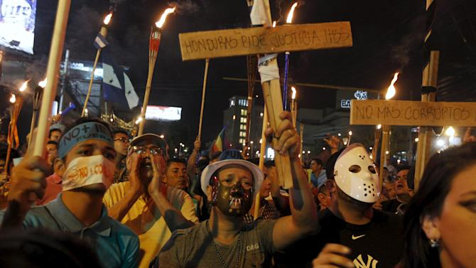 People holds crosses as they wear masks during a march to demand the resignation of Honduras' President Juan Hernandez in Tegucigalpa