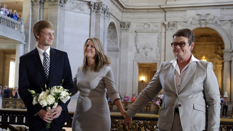 Sandy Stier, center, holds hand with partner Kris Perry, right, and their son Elliott after they were wed by California Attorney General Kamala Harris at City Hall in San Francisco, Friday, June 28, 2013. Stier and Perry, the lead plaintiffs in the U.S. Supreme Court case that overturned California's same-sex marriage ban, tied the knot about an hour after a federal appeals court freed same-sex couples to obtain marriage licenses for the first time in 4 1/2 years. (AP Photo/Marcio Jose Sanchez)