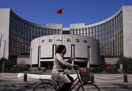 A woman rides past the headquarters of the People's Bank of China in Beijing