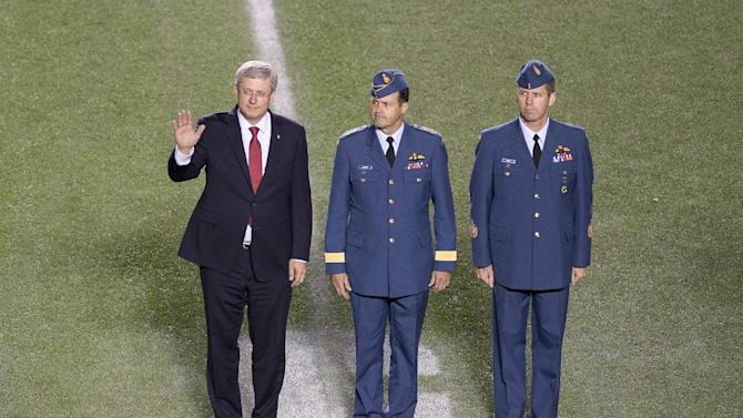 From left to right, Canada's Prime Minister Stephen Harper, Chief of the Defence Staff of the Canadian Armed Forces Gen. Tom Lawson  and Chief Warrant Officer Kevin West take part in a pregame ceremony in tribute to two fallen Canadian Armed Forces members before a CFL football game in Ottawa, Ontario, Friday, Oct. 24, 2014