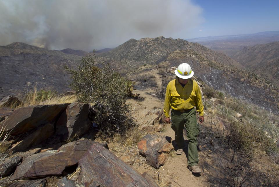 Todd Lerke with the U.S. Forest Service  walks a ridge as he works against the wildfire as it burns in the Bradshaw Mountains in the Prescott National Forest, Ariz. Wednesday, May 16, 2012. (AP Photo/The Arizona Republic, David Wallace)  MARICOPA COUNTY OUT; MAGS OUT; NO SALES