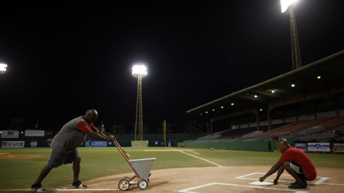 In this photo taken Dec. 29, 2012, workers prep a baseball field prior to a game in Caguas, Puerto Rico. The island has seen a resurgence of interest in baseball after 17-year-old shortstop Carlos Correa became the first Puerto Rican to be the first overall pick in this year's draft, receiving a $4.8 million signing bonus with the Houston Astros in June.  (AP Photo/Ricardo Arduengo)