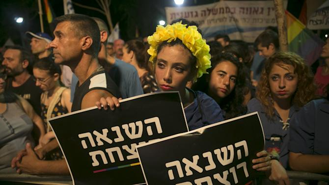 A woman holds signs during a protest  against the violence towards the gay community in Tel Aviv