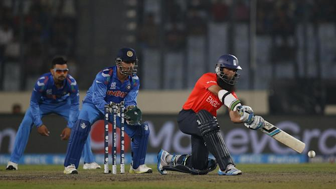 England batsman Moeen Ali, right, plays a shot as India's captain Mahendra Singh Dhoni, center, and Virat Kohli take positions during their ICC Twenty20 Cricket World Cup warm up match in Dhaka, Bangladesh, Wednesday, March 19, 2014. (AP Photo/Aijaz Rahi)
