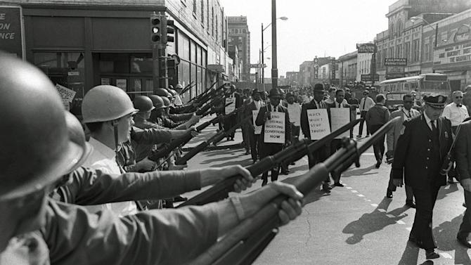 FILE -In this March 29, 1968 file photo, striking Memphis sanitation workers march past Tennessee National Guard troops with fixed bayonets during a 20-block march to City Hall, one day after a similar march erupted in violence, leaving one person dead and several injured. Forty-five years after Martin Luther King Jr. was killed supporting a historic sanitation workers strike in Memphis, the city's garbage and trash collectors are fighting to hold on to jobs that some city leaders want to hand over to a private company. (AP Photo/Charlie Kelly, File)
