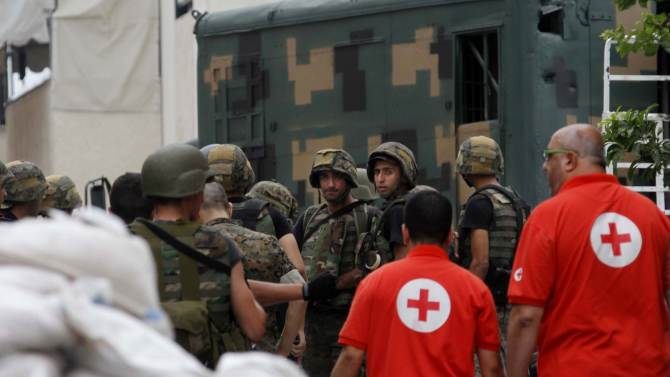 Lebanese red cross workers arrive to carry the lifeless bodies of gunmen killed during Monday's clashes with army soldiers near the Bilal bin Rabbah mosque where Sunni cleric Sheik Ahmad al-Assir preaches, in the southern port city of Sidon, Lebanon, Tuesday, June 25, 2013. Lebanese security officials say a roadside bomb has exploded on the highway linking Beirut with the Syrian capital without causing casualties. (AP Photo/Mohammed Zaatari)