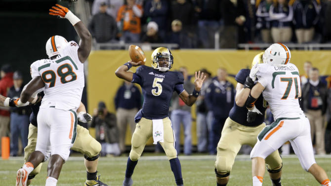 Notre Dame quarterback Everett Golson (5) passes between the Miami defense of defensive lineman Darius Smith, left, and defensive lineman Anthony Chickillo (71) during the first half of an NCAA college football game at Soldier Field Saturday, Oct. 6, 2012, in Chicago. (AP Photo/Charles Rex Arbogast)