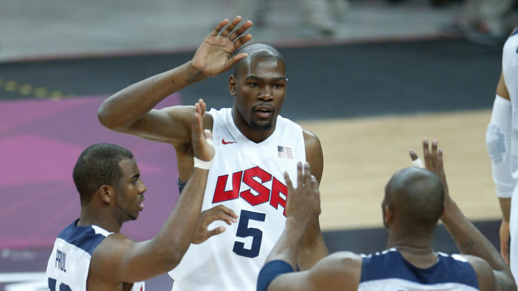 United States' Kevin Durant (5), Chris Paul (13) and Kobe Bryant (10) react during the first half of a preliminary men's basketball game against France at the 2012 Summer Olympics, Sunday, July 29, 2012, in London. The U.S. men beat France 98-71. (AP Photo/Jae C. Hong)