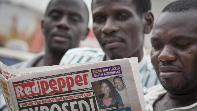"A Ugandan reads a copy of the ""Red Pepper"" tabloid newspaper in Kampala, Uganda Tuesday, Feb. 25, 2014. The Ugandan newspaper published a list Tuesday of what it called the country's ""200 top"" homosexuals, outing some Ugandans who previously had not identified themselves as gay, one day after the president Yoweri Museveni enacted a harsh anti-gay law. (AP Photo/Rebecca Vassie)"