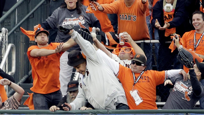 Fans try and catch a home run hit by San Francisco Giants' Pablo Sandoval during the first inning of Game 1 of baseball's World Series against the Detroit Tigers Wednesday, Oct. 24, 2012, in San Francisco. (AP Photo/David J. Phillip)
