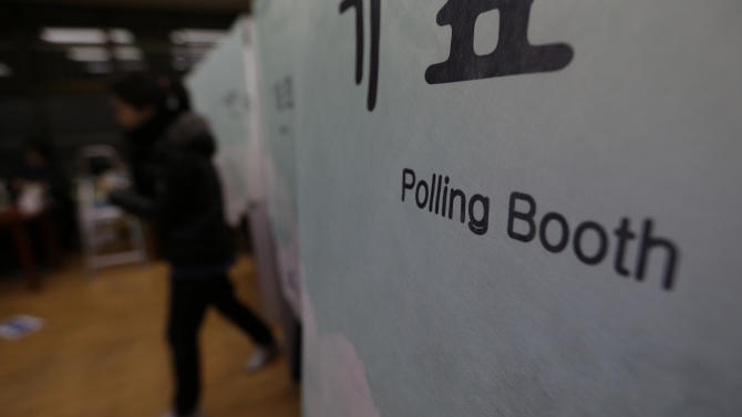 A South Korean woman leaves after her vote for the presidential election at a local polling station in Seoul, South Korea, Wednesday, Dec. 19, 2012. South Korea's closely contested presidential election  will determine how it will pursue relations with neighbors North Korea and Japan, and if it will have its first female leader. (AP Photo/Lee Jin-man)