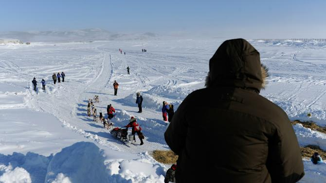 Spectators watch as Aliy Zirkle leaves Unalakleet, Alaska, during the Iditarod Trail Sled Dog Race on Sunday, March 11, 2012. (AP Photo/Anchorage Daily News, Marc Lester)