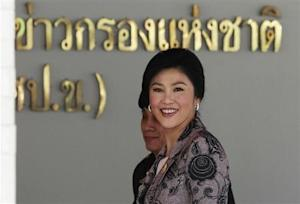 Thailand's PM Yingluck smiles as she arrives at Internal Security Operations Command in Bangkok