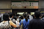 Commuters wait on the platform to board a train during peak hour in Singapore. The number of foreign workers in Singapore has risen by about 100,000 as of then end of June this year from a year ago despite measures to slow their influx, government data showed