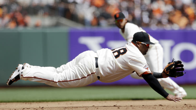 San Francisco Giants third baseman Pablo Sandoval makes a diving stop on a ground ball from St. Louis Cardinals' Allen Craig during the first inning of a baseball game on Friday, April 5, 2013 in San Francisco. Sandoval threw out Craig at first base. (AP Photo/Marcio Jose Sanchez)