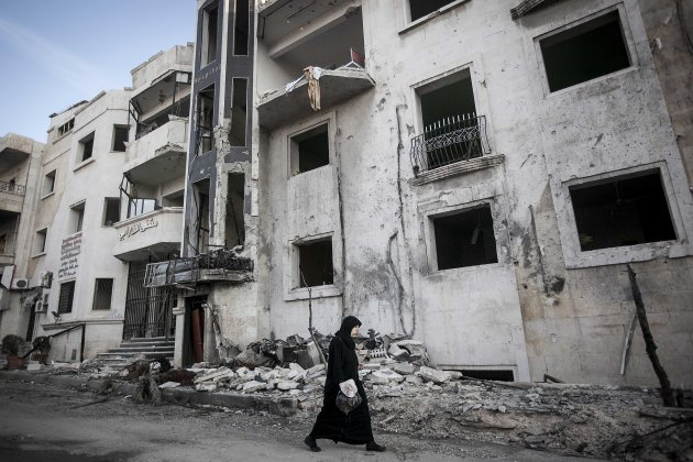 In this Saturday, Nov. 17, 2012 photo, a Syrian woman walks in front of a destroyed hospital where heavy clashes took place between rebel fighters and the Syrian army to seize control over the area, o