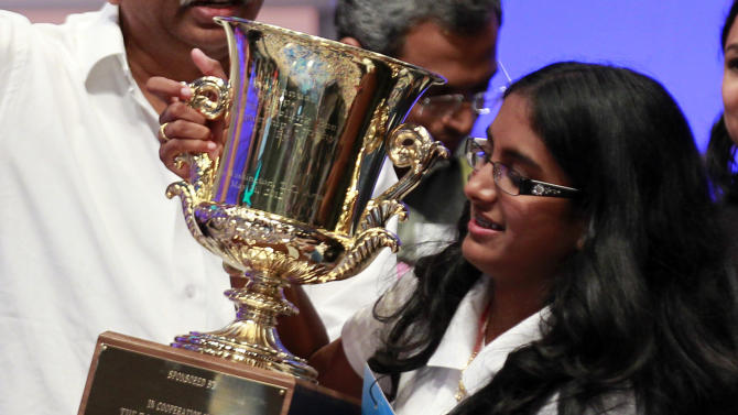 """Snigdha Nandipati, 14, of San Diego, holds the trophy after winning the National Spelling Bee with the word """"guetapens"""" Thursday, May 31, 2012 in Oxon Hill, Md. (AP Photo/Alex Brandon)"""
