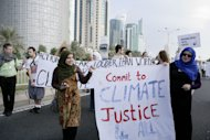 Qatari Women activists holding a banner reading &quot;commit to climate justice 4 all &quot; as they march with local and international activists march to demand urgent action to address climate change at the U.N. climate talks in Doha, Qatar, Saturday , Dec. 1, 2012. (AP Photo/Osama Faisal)