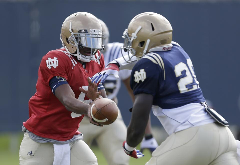 Notre Dame quarterback Everett Golson, left, hands off to running back Cierre Wood during practice, Friday, Jan. 4, 2013, at the Miami Dolphins' training facility in Davie, Fla. Notre Dame will play Alabama on Monday, Jan. 7, in the BCS national championship NCAA college football game. (AP Photo/Wilfredo Lee)