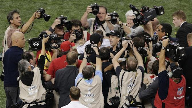 Photographers surround Baltimore Ravens head coach John Harbaugh, right, and San Francisco 49ers head coach Jim Harbaugh as they shake hands after the NFL Super Bowl XLVII football game, Sunday, Feb. 3, 2013, in New Orleans. The Ravens won 34-31. (AP Photo/Charlie Riedel)