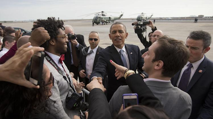 President Barack Obama greets supporters on the tarmac upon his arrival on Air Force One, Tuesday, March 11, 2014, at JFK International Airport in New York. Obama traveled to New York for a pair of fundraisers for the Democrats. (AP Photo/Pablo Martinez Monsivais)