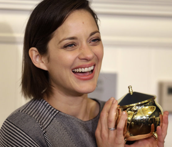 Hasty Pudding Woman of the Year, actress Marion Cotillard, of France, holds the award during a news conference, at Harvard University, in Cambridge, Mass., Thursday, Jan. 31, 2013. The award was presented to Cotillard by Hasty Pudding Theatricals, a theatrical student society at Harvard. (AP Photo/Steven Senne)