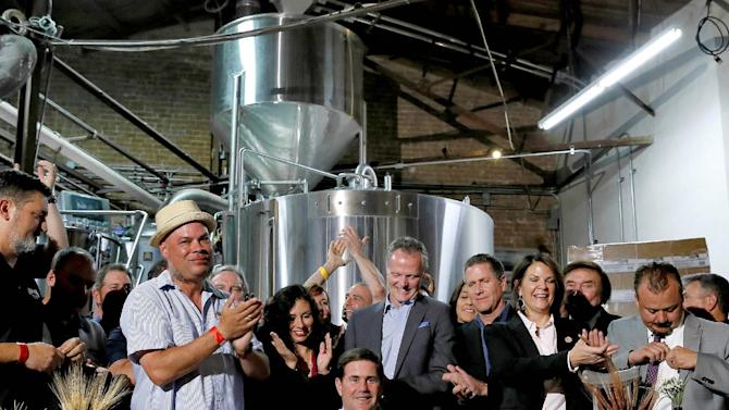 Supporters clap after Arizona Gov. Doug Ducey, center, signed Senate Bill 1030, Tuesday, March 31, 2015, at Four Peaks Brewery in Tempe, Ariz. The bill allows microbreweries to keep running their restaurants even as they grow into large beer producers. (AP Photo/Matt York)