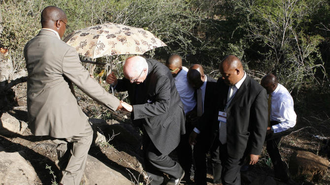 Retired judge Ian Farlam, centre, is assisted by unknown aid as he inspects the area where the bodies of mine workers were found, after the shootings at Lonmin's platinum mine in Marikana near Rustenburg, South Africa, Monday, Oct. 1, 2012.  An official inquiry into the killings of dozens of people near a South African platinum mine began Monday even as labor unrest continued with workers at other mines as well as truck drivers continuing protests over pay. (AP Photo/Themba Hadebe)