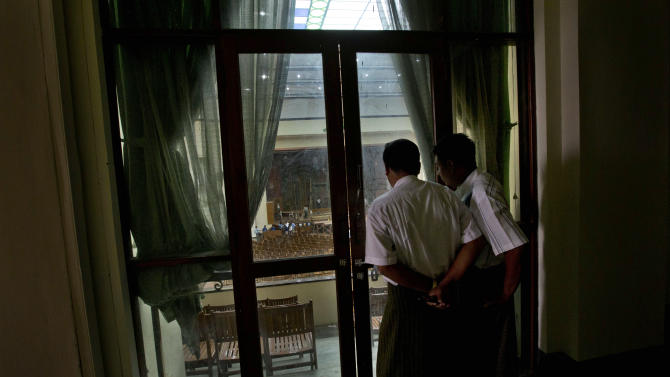 In this picture taken on Friday, Nov. 16, 2012, plain clothed men, believed to be Myanmar government security officers watch repair work from the balcony of Yangon University's Convocation Hall, in Yangon, Myanmar. Inside the hall, where President Barack Obama will deliver a speech on Monday, Nov. 19, 2012, is a riot of staple guns, buzz saws, sandpaper, hammers, spackle, drills, brooms, and fresh paint.  But the facade of the building remains cracked with a black crust. Local superstition holds that scrubbing the building clean would unbalance the resigned calm that has settled on the campus and spark another round of unrest. (AP Photo/Gemunu Amarasinghe)