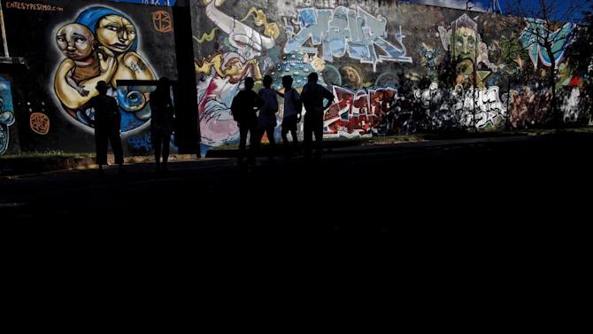 In this March 2, 2013 photo, Matt Fox Tucker, second from left, shows to tourists a mural by Peruvian street artist Entes, left, and a mural by artist Oz and Ice, right, as he gives a tour of street art in Buenos Aires Argentina. Fox-Tucker is an Englishman who created the website buenosairesstreetart.com that focuses on urban murals around the city. (AP Photo/Natacha Pisarenko)