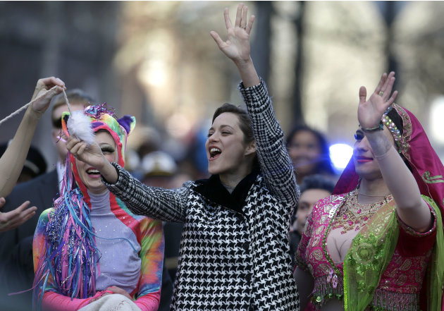 Actress Marion Cotillard, of France, center, the Hasty Pudding Woman of the Year, waves to the crowd as Harvard University theatrical students Renee Rober, left, and Ben Moss, right, ride with her in
