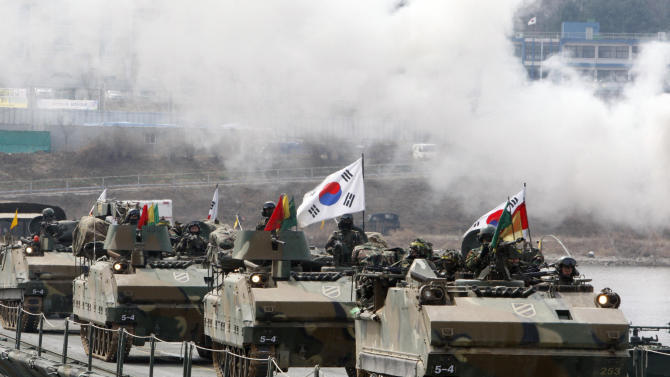 South Korean Army armored vehicles cross a pontoon bridge during an exercise against possible attacks by North Korea near the demilitarized zone (DMZ) in Hwacheon, South Korea  Monday, April 1, 2013.  After weeks of war-like rhetoric, North Korean leader Kim Jong Un gathered legislators Monday for an annual spring parliamentary session taking place one day after top party officials adopted a statement declaring building nuclear weapons and the economy the nation's top priorities.(AP Photo/Yonhap, Lee Hae-ryong)  KOREA OUT