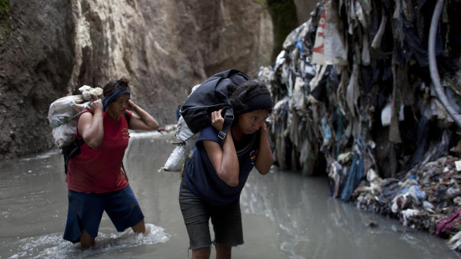 """In this photo taken Tuesday Oct. 6, 2011, Irma, 29, right, and Dora, 30, carry sacks of metal they collected after working all night in contaminated water at the bottom of one of the biggest trash dumps in the city, known as """"The Mine,"""" in  Guatemala City.  Hundreds of informal workers descend daily into the mounds of the landfill and the rushing waters that come from a storm tunnel and a sewer at the bottom of a gorge to search for scrap metal to sell. This activity known locally as """"mining"""" is extremely dangerous due to mud slides and collapses, but earns many of them about 150 quetzals ($20 dollars) a day, nearly twice the minimum daily wage. AP Photo/Rodrigo Abd)"""