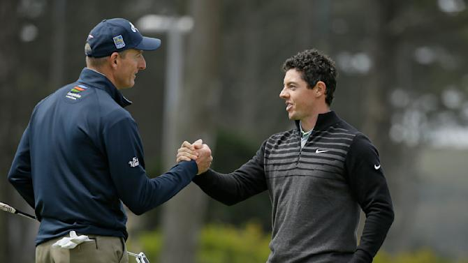 Rory McIlroy, right, of Northern Ireland, is greeted by Jim Furyk, left, on the 18th green of TPC Harding Park at the end of their semifinal  match at the Match Play Championship golf tournament Sunday, May 3, 2015, in San Francisco. McIlroy won the match. (AP Photo/Eric Risberg)