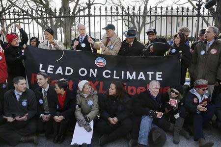 Bond, Brune and activists opposed to the Keystone XL tar sands pipeline project tie themselves to the White House fence during an environmental protest in Washington