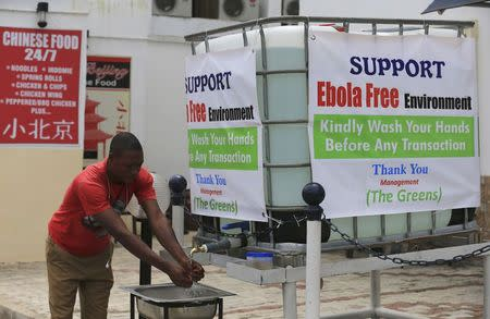 A man washes his hands at a tap outside the Green Pharmacy at Area 8 in Abuja