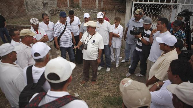 Vigilante leader Hipolito Mora talks to other vigilantes before they leave to voluntarily cooperate in a shootout investigation in La Ruana, Michoacan