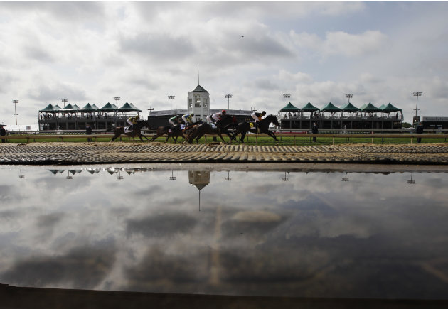 Water covers the ground on the outside of the track after heavy overnight rain during the first race of the day before the 138th Kentucky Derby horse race at Churchill Downs Saturday, May 5, 2012, in