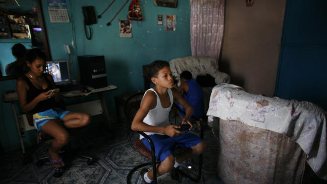 In this June 1, 2012 photo, young boxer Miguel Uzcategui, 13, plays a game on his PlayStation at home in the San Agustin slum in Caracas, Venezuela. Every weekend, boys line up with their gloves to slug it out in a boxing ring that moves around Caracas from parks to plazas to streets in the slums. They're participating in a program supported by the Venezuelan government that aims not only to develop standout fighters but also to expand the sport's reach and give poor teenagers an outlet to stay away from crime, alcohol and drugs. Uzcategui says the sport has given him goals as well as improved self-confidence.  (AP Photo/Ariana Cubillos)