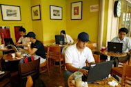 "Photo illustration shows people surfing the Internet at a coffee shop in Kuala Lumpur. Malaysian NGOs, well-known bloggers and opposition politicians on Tuesday staged a one-day ""Internet blackout"" to protest a legal amendment that they say threatens free expression on the Web"