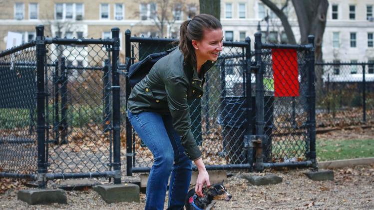 Kristin Douglas, a dog-sitter for Gigi, a Rat Terrier, pats Gigi inside a dog walk in New York