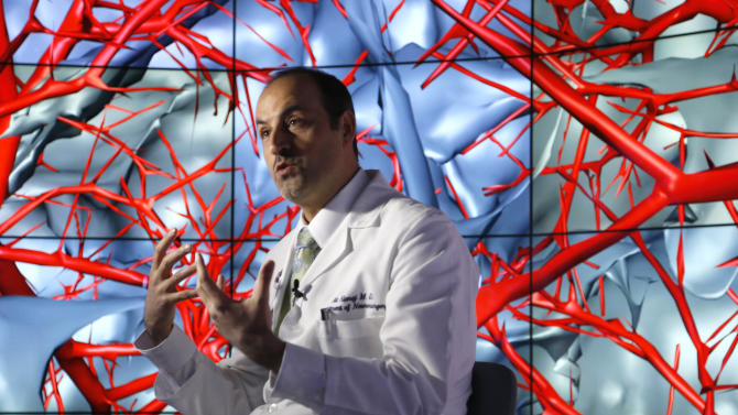 """In this photo taken Thursday, Jan. 24, 2013, in Chicago, brain surgeon Ali Alaraj talks about the first time he viewed the brain using the CAVE2. """"You can walk between the blood vessels,"""" said the University of Illinois College of Medicine neurosurgeon. """"You can look at the arteries from below. You can look at the arteries from the side"""". CAVE2 is a system of 72 stereoscopic liquid crystal display panels that encircles the viewer 320 degrees and creates a 3D environment that can take you to the bridge of the Starship Enterprise, a flyover of the planet Mars, or through the blood vessels of the brain. (AP Photo/Charles Rex Arbogast)"""