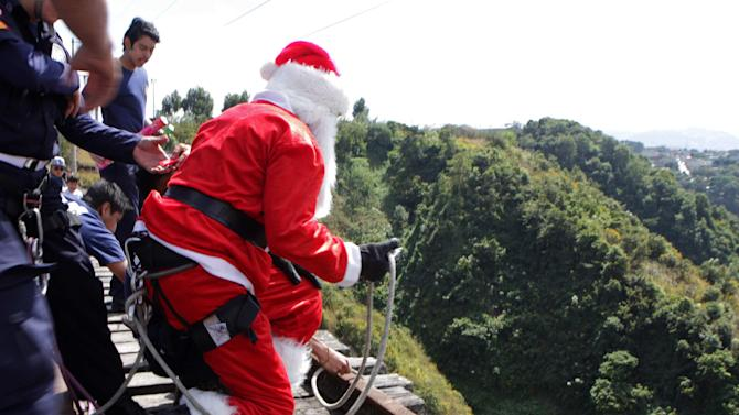 Guatemalan firefighter Chacon, wearing a Santa Claus outfit, prepares to rappel down from the Belize bridge to give toys to children living under the bridge, in Guatemala City