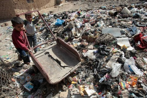 Iraqi children play on a garbage dump at the Mukhayamat settlement in north Baghdad