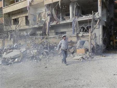 A man carrying a shovel, walks near buildings damaged after what activists said was a Syrian Air Force fighter jet operated by those loyal to Syria's President Bashar al-Assad, fired missiles in Daria, near Damascus November 29, 2012. Picture taken November 29. REUTERS/Kenan Al-Derani/Shaam News Network/Handout