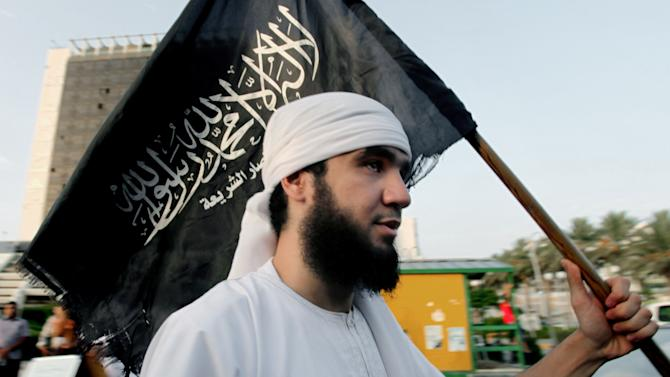 """FILE -- In this Friday, Sept. 14, 2012 file photo, a Libyan follower of Ansar al-Shariah Brigades chants as he carries the Brigades flag, with Arabic writing that reads, """"There is no God but Allah and Muhammad is his messenger, Ansar al-Shariah,"""" during a protest in front of the Tibesti Hotel, in Benghazi, Libya. Libya's upheaval the past two years helped lead to the ongoing conflict in Mali, and now Mali's war threatens to wash back and further hike Libya's instability. There is a growing fear that post-Moammar Gadhafi Libya is becoming an incubator of turmoil, with an overflow of weapons and Islamic jihadi militants operating freely, ready for battlefields at home or abroad. (AP Photo/Mohammad Hannon, File)"""