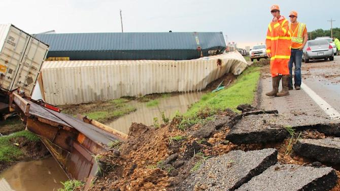Highway workers inspect the damage to Hwy. 49in Otwell, Ark. after high winds derailed more than adozen train cars on Thursday, June 5, 2014. Strong winds and flooding led to the deaths of at least three people in the South on Thursday as powerful thunderstorms moved through the region. (AP Photo/The Sun, Staci Vandagriff)